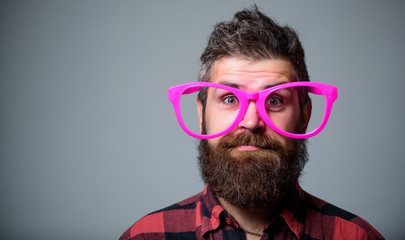 Nerd concept. Hipster looking through of giant pink eyeglasses. Man beard and mustache face wear funny big eyeglasses. Life in pink color. Naivety man. Naivety and simplicity. Adult but still naivety