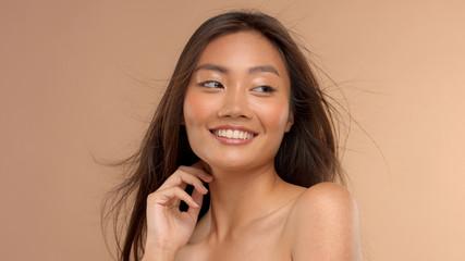 laughing asian model watching aside