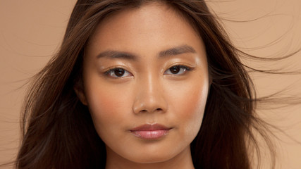 closeup portrait of asian, thai jepenese, corean model watching to the camira with blowing hair