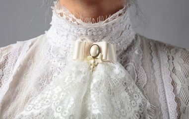 Fragment of a Victorian dress with a brooch.