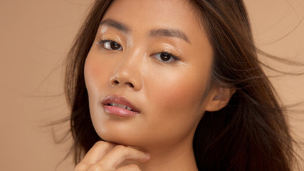 closeup portrait of asian, thai jepenese, corean model watching to the camira with blowing hair with fase slightly turned to the left