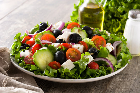 Fresh Greek salad in bowl with black olive,tomato,feta cheese, cucumber and onion on wooden table.