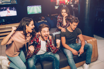 Picture of happy couple cheering while second is upset. They win and lost game. Guys hold gamepads in hands. They sit together in playing room.