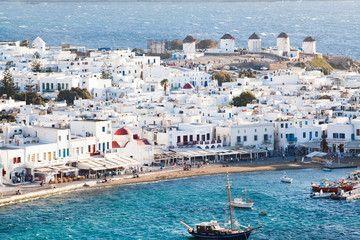 panoramic view of the Mykonos town harbor with famous windmills from the above hills on a sunny summer day, Mykonos, Cyclades, Greece