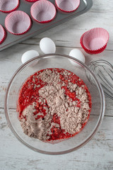 red velvet cake batter with ingredients and cupcake tin flat lay