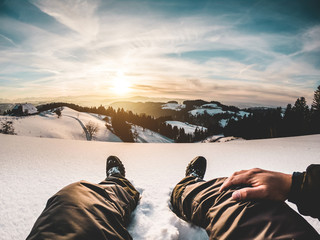 Pov view of young man looking the sunset on snow high mountains