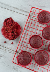 baked red velvet cupcakes on red wire rack flat lay