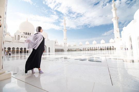Traditionally dressed arabic woman wearing black burka visiting Sheikh Zayed Grand Mosque in Abu Dhabi, United Arab Emirates.