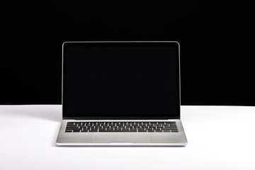 laptop with blank screen on white desk isolated on black
