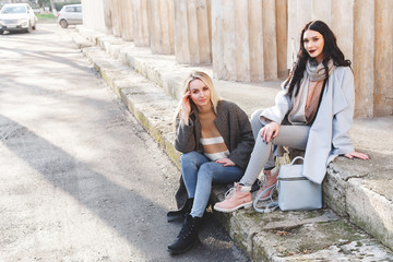Two young beautiful girls, blonde and brunette, in gray and blue coat sitting on the steps. Two girl friends relaxing outdoors in the city. Fashion, street casual outfit.