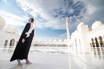 Poster Abou Dabi Traveling by United Arabic Emirates. Young woman in traditional abaya standing in the Sheikh Zayed Grand Mosque, famous Abu Dhabi sightseeing.