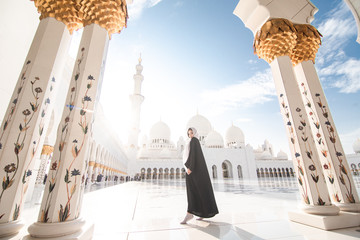 Traveling by United Arabic Emirates. Young Woman in traditional abaya standing in the Sheikh Zayed Grand Mosque, famous Abu Dhabi sightseeing.