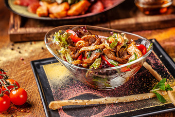 The concept of Indian cuisine. Warm salad with beef and chicken, bell pepper and honey mint sauce. Serving dishes in a restaurant in a glass plate. On a wooden table. background image.