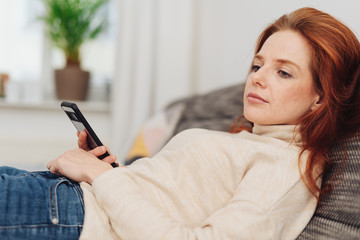 Attractive woman reading a message on her mobile