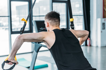 back view of athletic young man training with resistance bands in gym