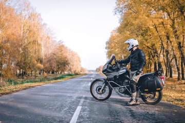 Biker man in leather jacket and black tourist motorcycle with side bags. wallpaper concept, enduro advetnture, space for text, autmn season