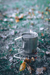 Tourist equipment and tools, camping gas, cooking in a hike, coffee tea in a metal cup. background concept of tourism and adventure, autmn season