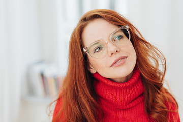 Pensive young redhead woman wearing glasses