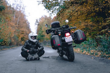 Poster Motorise Biker man in leather jacket and black tourist motorcycle with side bags. wallpaper concept, enduro advetnture, space for text, autmn season, problems on the road accident