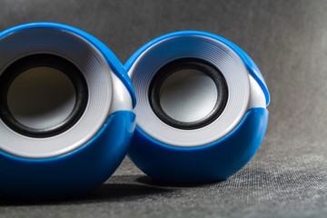 Portable small speakers for music. Plastic. Black background. Blue and white colors. Round shape. Modern equipment. Technologies.