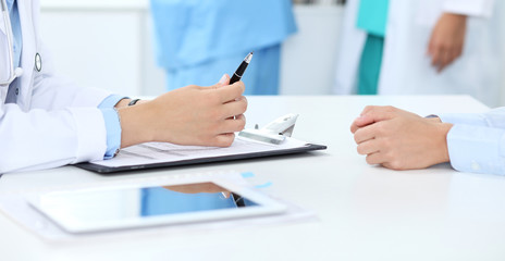 Doctor and patient discussing something, just hands at the table, white background