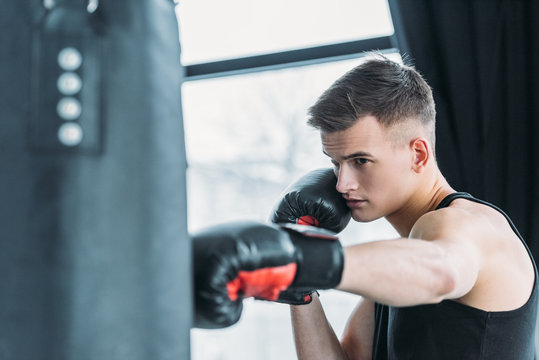 concentrated young sporty man boxing with punching bag in gym