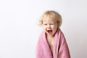 portrait of a cute curly caucasian girl wrapped in a terry towel laughing after bath isolated on white background. childcare concept