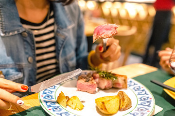 Woman eating delicious rare beef steak in restaurant
