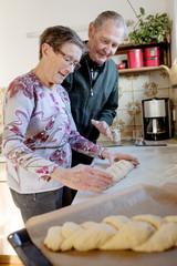Seniorenpaar backt zuhause ein Brot