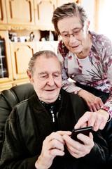 Senior, Seniorin, Seniorenpaar surft gemeinsam auf einem Smarphone im Internet