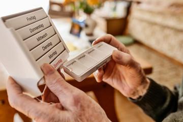 Senior nimmt seine Tabletten ein aus einer Medikamentenbox