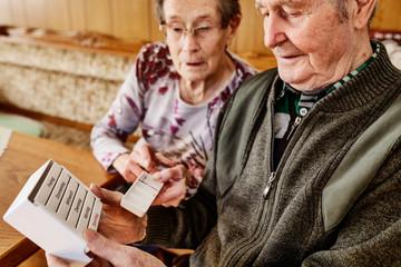 Seniorin hilft ihrem Mann, Senior, bei der Einnahme der Medikamente,