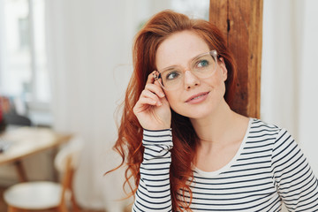 Attractive woman holding her hand to her glasses