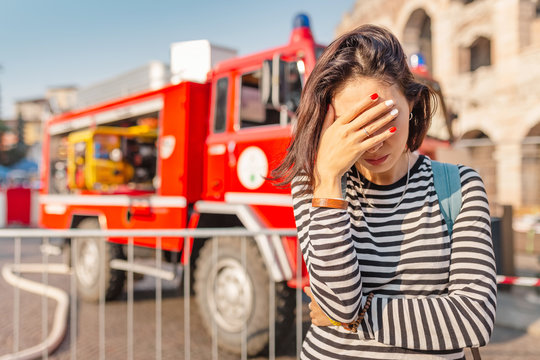 A woman in stress covers her face with her hands on the background of a fire fighting truck. Accident and insurance concept