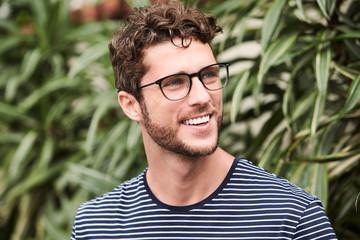 Smiling guy in glasses, looking away Wall mural