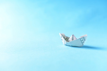Origami boat made of dollar banknote on color background 765ce54099