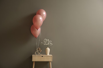 Table with vase and balloons on grey background
