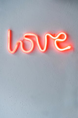 Red Neon Love Sign on a white wall. Selective focus.