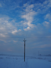 Electric support and crossed wires on a background of blue sky, vertical view