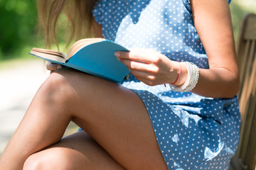 Woman in a blue dress sitting on a bench in a city park and reading a book