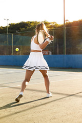 Female tennis player in white about to hit ball