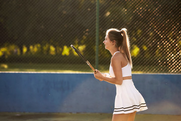Female tennis player in white, side view