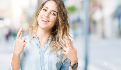 Beautiful young blonde woman over isolated background smiling crossing fingers with hope and eyes closed. Luck and superstitious concept.