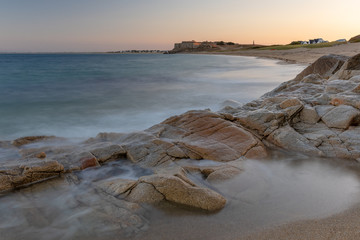 French landscape - Bretagne. A beautiful beach with rocks and fortress in the background at sunrise.