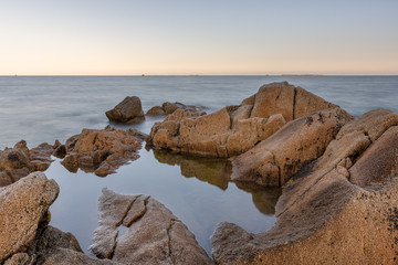 French landscape - Bretagne. A beautiful formation of rocks and the sea in the background at sunrise.