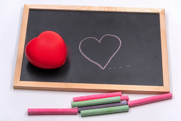 Soft heart ball put on blackboard,Color chalk draw cartoon heart shape on blackbroad.Tell love in valentine day or tell save good health and heart.