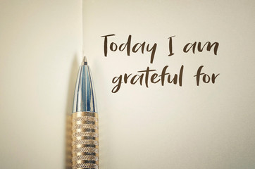 Close up of gratitude word with pen on notebook