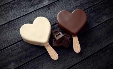Two ice creams with heart shape and ounces of chocolate on wood
