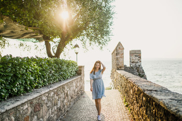 young beautiful girl with red hair in a blue dress walks at sunrise on the seashore