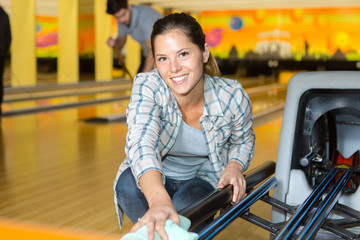 female employee cleaning bowling alley